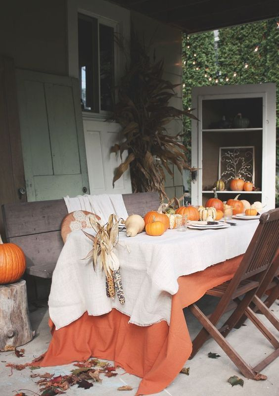 a bright fall tablescape with a white and an orange tablecloth, pumpkins, corn cobs and plates and placemats
