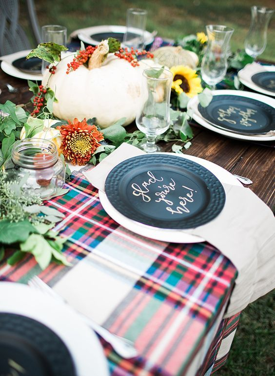 a bright fall tablescape with plaid touches, a large pumpkin, bright blooms and greenery and candles in jars