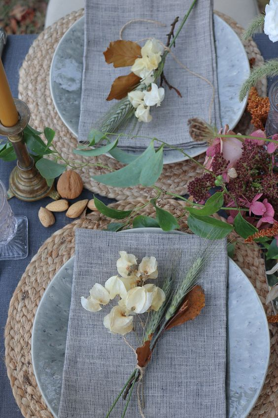 a bright vintage Thanksgiving tablescape with woven placemats, neutral linens, nuts, acorns, bright blooms and candles