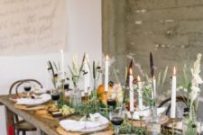 a chic Thanksgiving tablescape with woven placemats, tall candles, a greeneyr runner and some pumpkins