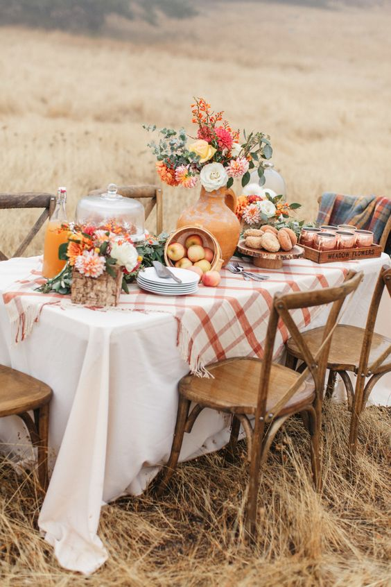 a chic and bright Thanksgiving table with bright florals, white pumpkins in cloches and a plaid tablecloth