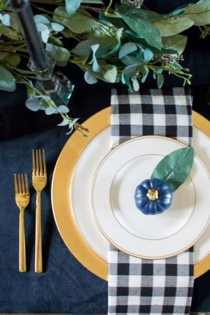 a chic farmhouse Thanksgiving tablescape with a navy tablecloth, plaid napkins, a navy pumpkin, a gold charger and gold cutlery