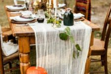 a chic natural Thanksgiving table with a runner, fresh pumpkins, tall candles and some leaves and vases