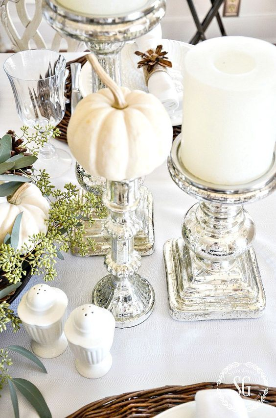 a chic neutral Thanksgiving tablescape with mini pumpkins, large candles, mercury glass candleholders and some greenery