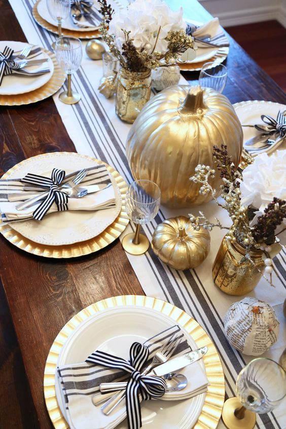 a chic rustic Thanksgiving tablescape with a striped runner, gold chargers, striped napkins, gilded pumpkins and faux branches