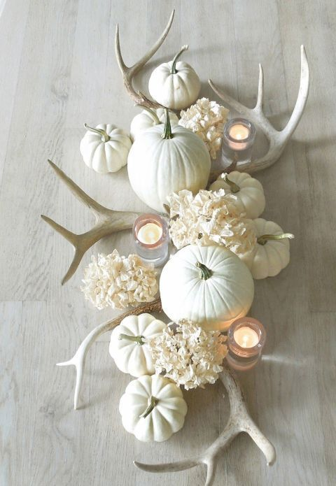 a chic white Thanksgiving centerpiece of white pumpkins, hydrangeas, antlers and candles is beautiful
