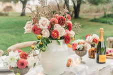 a colorful Thanksgiving table with a neutral runner, a bright floral centerpiece, fruits, candles and simple porcelain