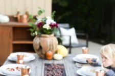 a cool wooden table with a wooden bowl with pumpkins and gourds, copper glasses and ugs and a floral centerpiece in a pumpkin