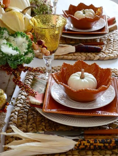 a cozy rustic Thanksgiving tablescape with woven placemats, white and orange plates, white pumpkins, corn cobs and veggies