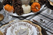 a cozy rustic vintage Thanksgiving tablescape with a plaid tablecloth, quote napkins, woven chargers, gold and pritned plates, a chic centerpiece of wheat, pumpkins and pinecones
