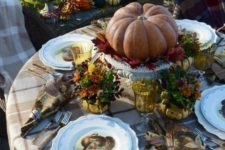 a cozy traditional Thanksgiving table with plaid textiles, bright blooms, printed plates and a pumpkin centerpiece