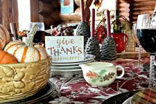 a cozy vintage-inspired Thanksgiving tablescape with a floral tablecloth, printed plates, a floral milk jug, pinecone candleholders and a bowl with pumpkins