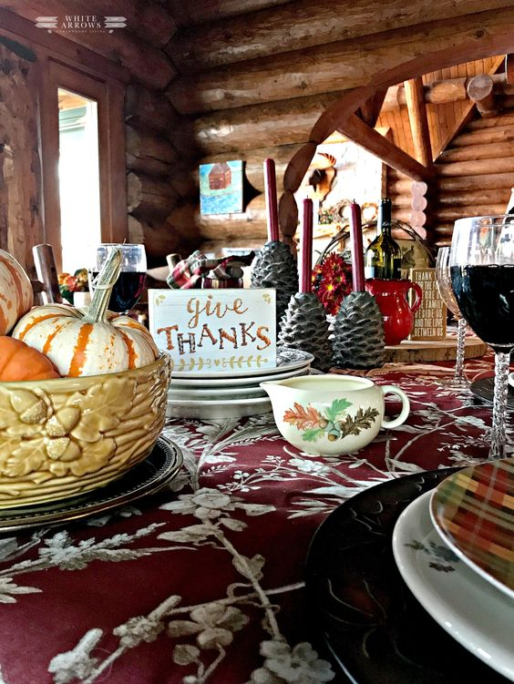 a cozy vintage inspired Thanksgiving tablescape with a floral tablecloth, printed plates, a floral milk jug, pinecone candleholders and a bowl with pumpkins