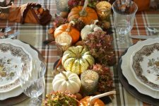 a cozy vintage rustic Thanksgiving tablescape with a plaid tablecloth, printed plates, natural pumpkins, leaves and hydrangeas, candles and nuts