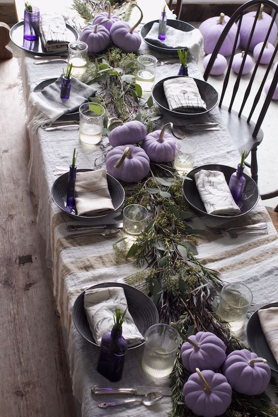 a creative and laid-back Thanksgiving tablescape with a linen striped tablecloth, a greenery runner, lilac pumpkins and lilac bottles with greenery