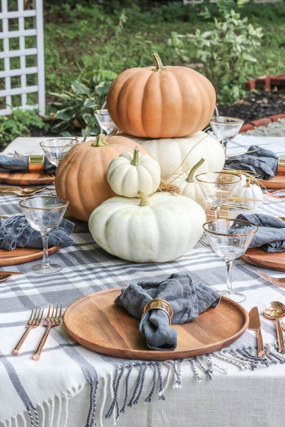 a cute and neutral tablescape with plaid linens, fresh pumpkins stacked and some hay on the table