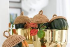 a gold polished bowl with gourds turned into oversized acorns using rope is a stylish and quirky centerpiece to rock for Thanksgiving