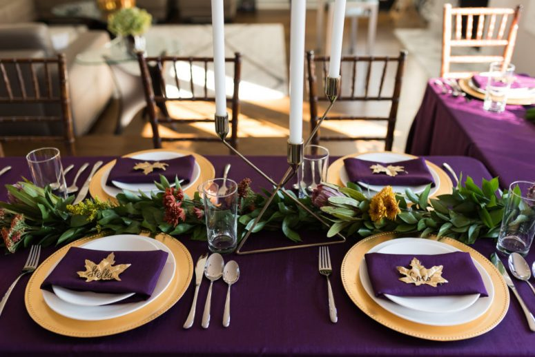 a gorgeous purple Thanksgiving tablescape with a purple tablecloth and napkins, a greenery and bright bloom runner, tall candles, gold touches and fall leaves