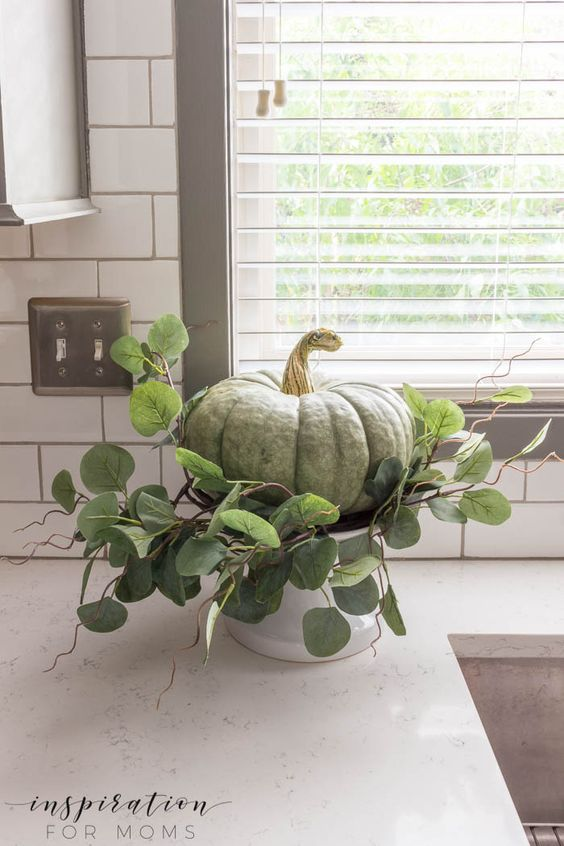 a green heirloom pumpkin with greenery on a stand for rustic Thanksgiving decor