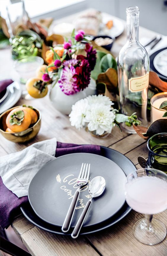 a laid-back and rustic Thanksgiving tablescape with greenery, bold purple blooms, fruits, black plates and purple napkins