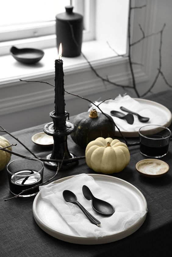 a minimalist Halloween table setting with black and white linens, black cutlery and candles, black and white pumpkins