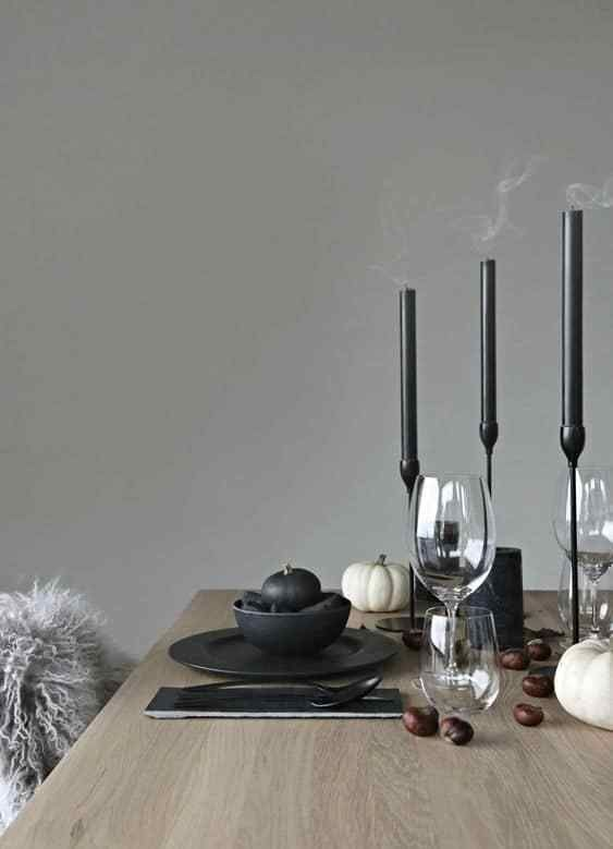 a minimalist Halloween tablescape with black candles in candleholders, black plates, cutlery, black and white pumpkins and acorns