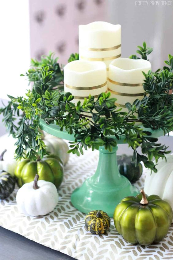 a modern Thanksgivving centerpiece of a green stand with greenery, striped candles, white and green pumpkins and a printed runner