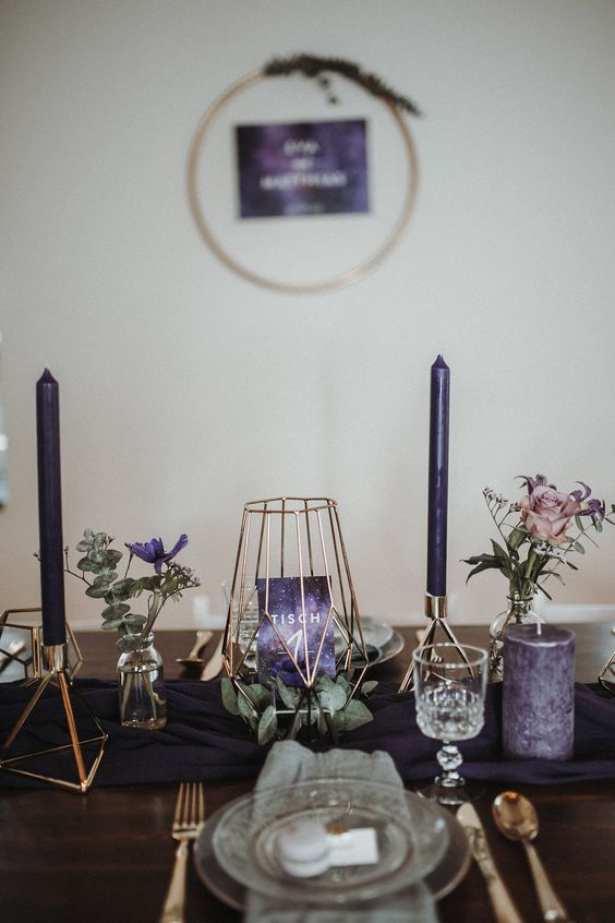 a modern and fresh purple Thanksgiving tablescape with purple candles, blooms and a table number, a deep purple table runner and gold cutlery
