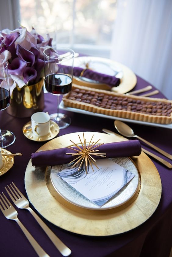 a modern glam Thanksgiving tablescape with a purple tablecloth, napkins and callas, gold charrgers and cutlery and a vase