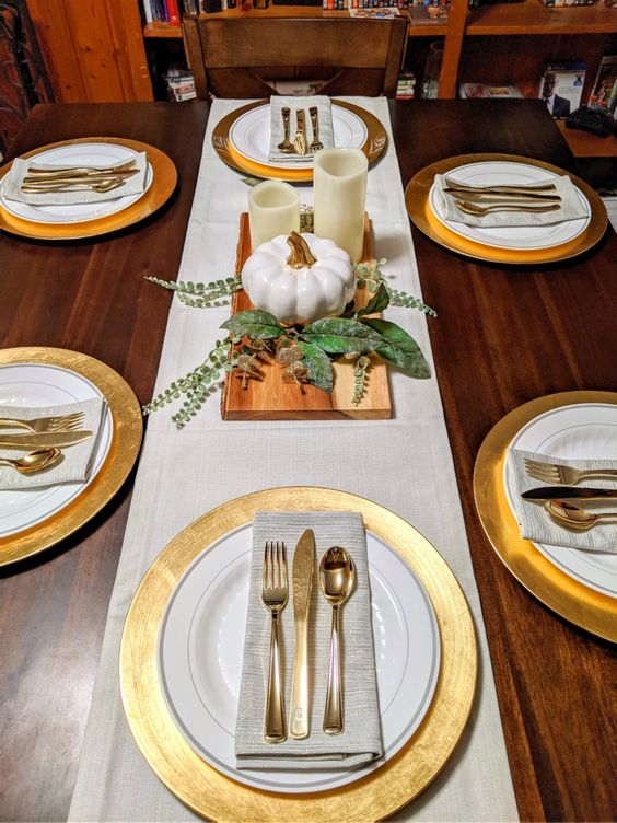 a modern rustic Thanksgiving tablescape with gold chargers, neutral linens, white candles and pumpkins and some greenery