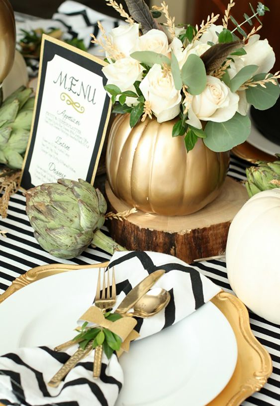 a modern rustic Thanksgiving tablescape with striped and chevron linens, gold chargers and cutlery, a white rose arrangement and artichokes
