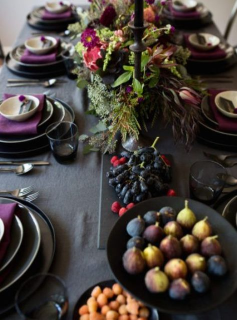 a moody Thanksgiving tablescape with a grey tablecloth, purple napkins, black plates and candles, black bowls with food