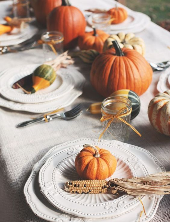 a natural tablescape with pumpkins, corn cobs, husks, candles and some elegant vintage plates