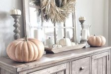 a neutral rustic Thanksgiving console table with a corn husk wreath, large and small pumpkins and candles