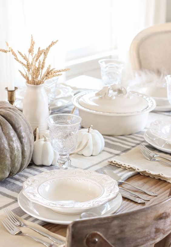 a neutral rustic Thanksgiving tablescape with a striped runner, white and taupe pumpkins, wheat and white porcelain