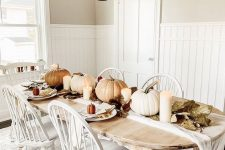 a neutral rustic vintage Thanksgiving table with neutral pumpkins, candles, leaves and simple white porcelain