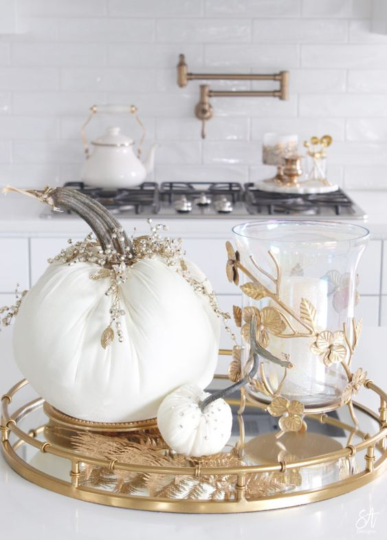a refined Thanksgiving centerpiece of a mirror and gold tray, white embellished fabric pumpkins and a candle ina glass candleholder