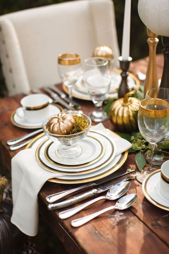 a refined Thanksgiving tablescape with gold rimmer plates and glasses plus gilded pumpkins is cool