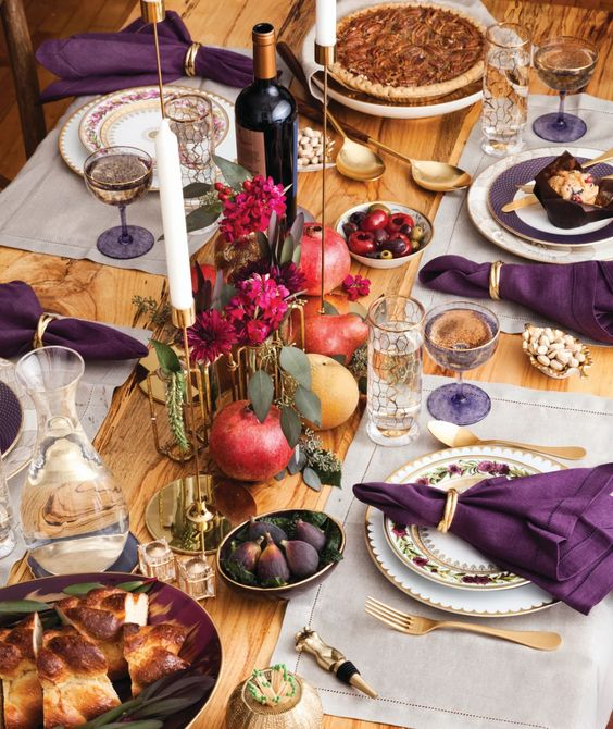a refined Thanksgiving tablescape with neutral placemats, purple napkins, bold fuchsia blooms, gold touches and berries