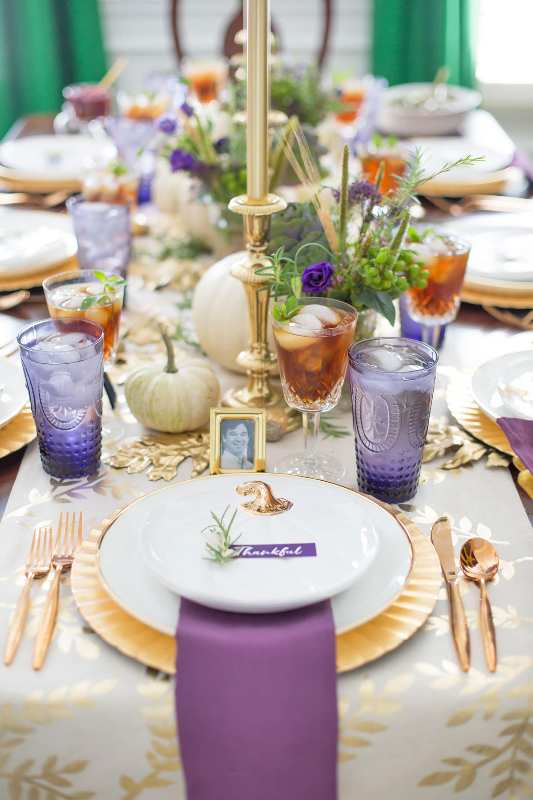 a refined gold and purple Thanksgiving tablescape with gold cutleyr, chargers and candlesticks, white pumpkins, greenery, purple glasses and napkins