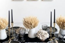a refined modern Thanksgiving tablescape with a black runner, black plates, black candles, wheat in jugs and some dried blooms