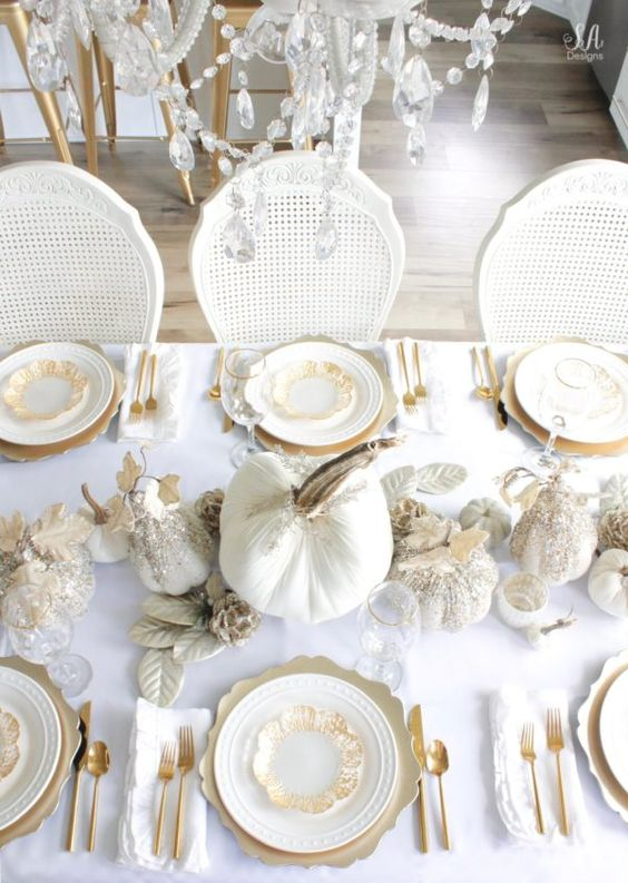 a refined white and gold Thanksgiving tablescape with white embellished pumpkins, white leaves, gold chargers and cutlery plus a crystal chandelier over the table