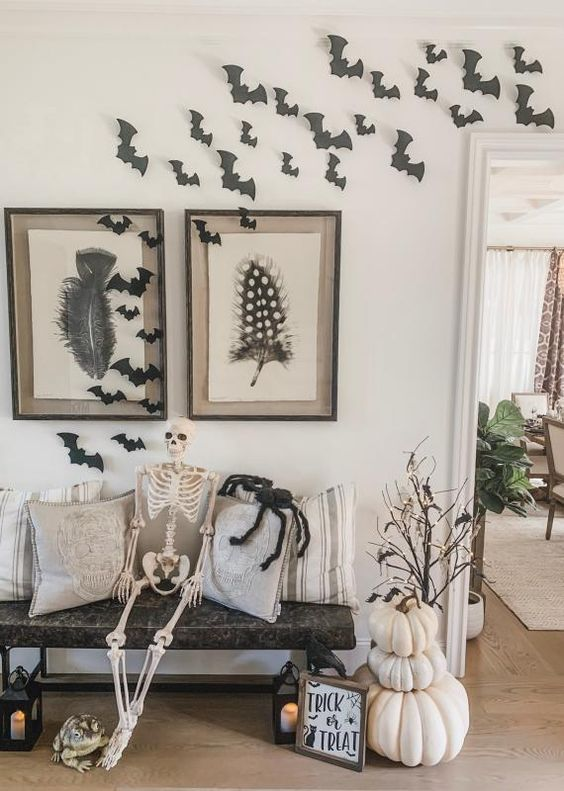 a rustic Halloween entryway with stacked white pumpkins, branches with lights, bats and a skeleton
