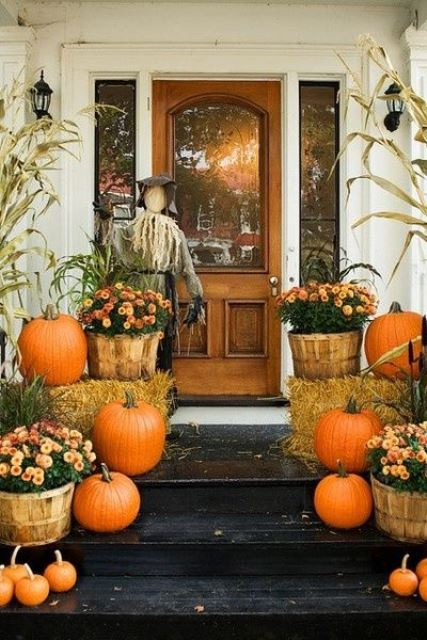 a rustic Halloween porch with a scarecrow, pumpkins, hay and bright blooms in wooden baskets