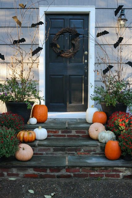 a rustic Halloween porch with natural pumpkins, a vine wreath with bats and branches with bats