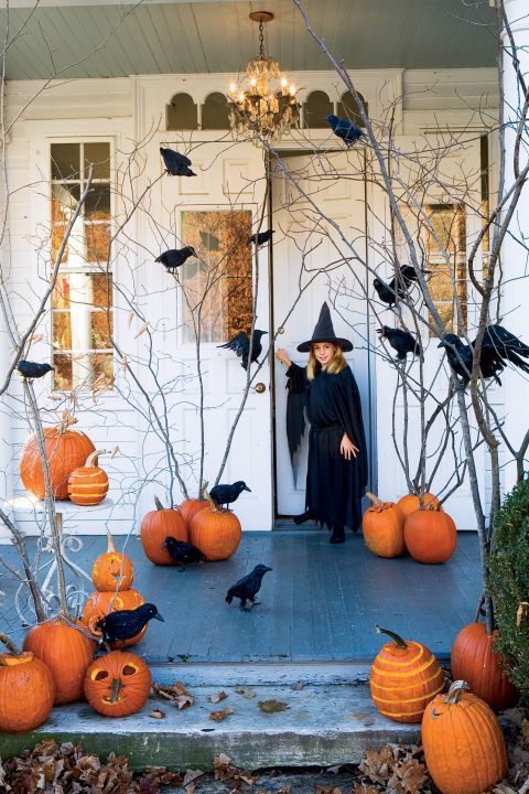 a rustic Halloween porch with orange pumpkins and branches, crows is a stylish fall space