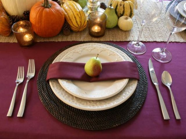 a rustic Thanksgiving table setting with a purple tablecloth and napkins, gourds, pumpkins, pears, candles and woven placemats