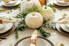 a rustic Thanksgiving table with wooden chargers, a burlap tablecloth, gold cutlery, white pumpkins and greenery plus candles
