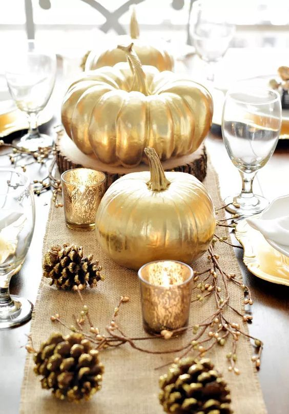 a rustic Thanksgiving tablescape with a burlap runner, berries on branches, gilded pinecones and creatively shaped plates