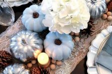 a rustic coastal Thanksgiving table with a lace runner, blue and silver pumpkins, white hydrangeas, pinecones and beads plus blue napkins